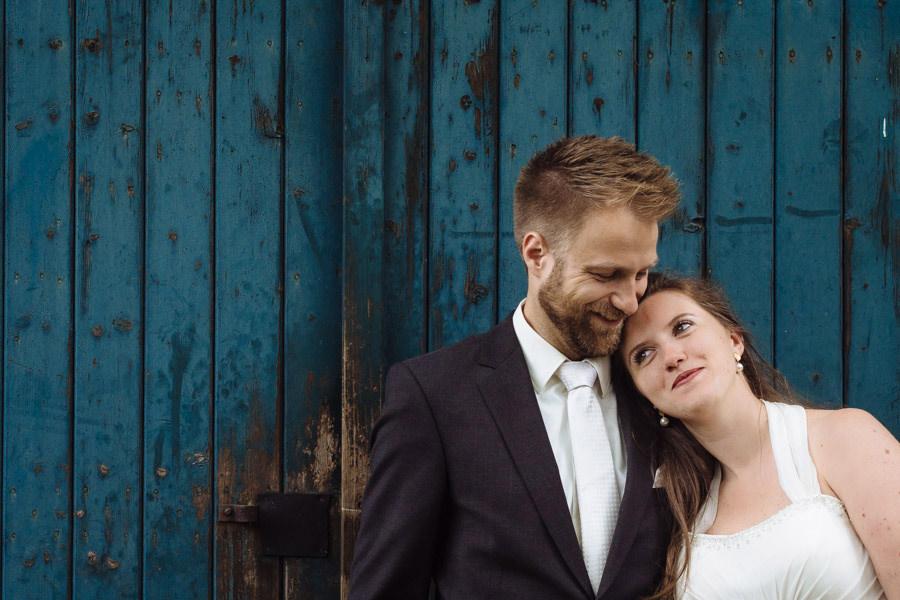 Kundenstimmen Hochzeitsfotografin Solingen mit Brautpaar vor blauer Wand