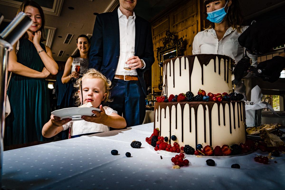 Blumenmaedchen probiert Hochzeitskuchen bei Hochzeit Deichgraf Duesseldorf mit beste Hochzeitsfotograf Duesseldorf