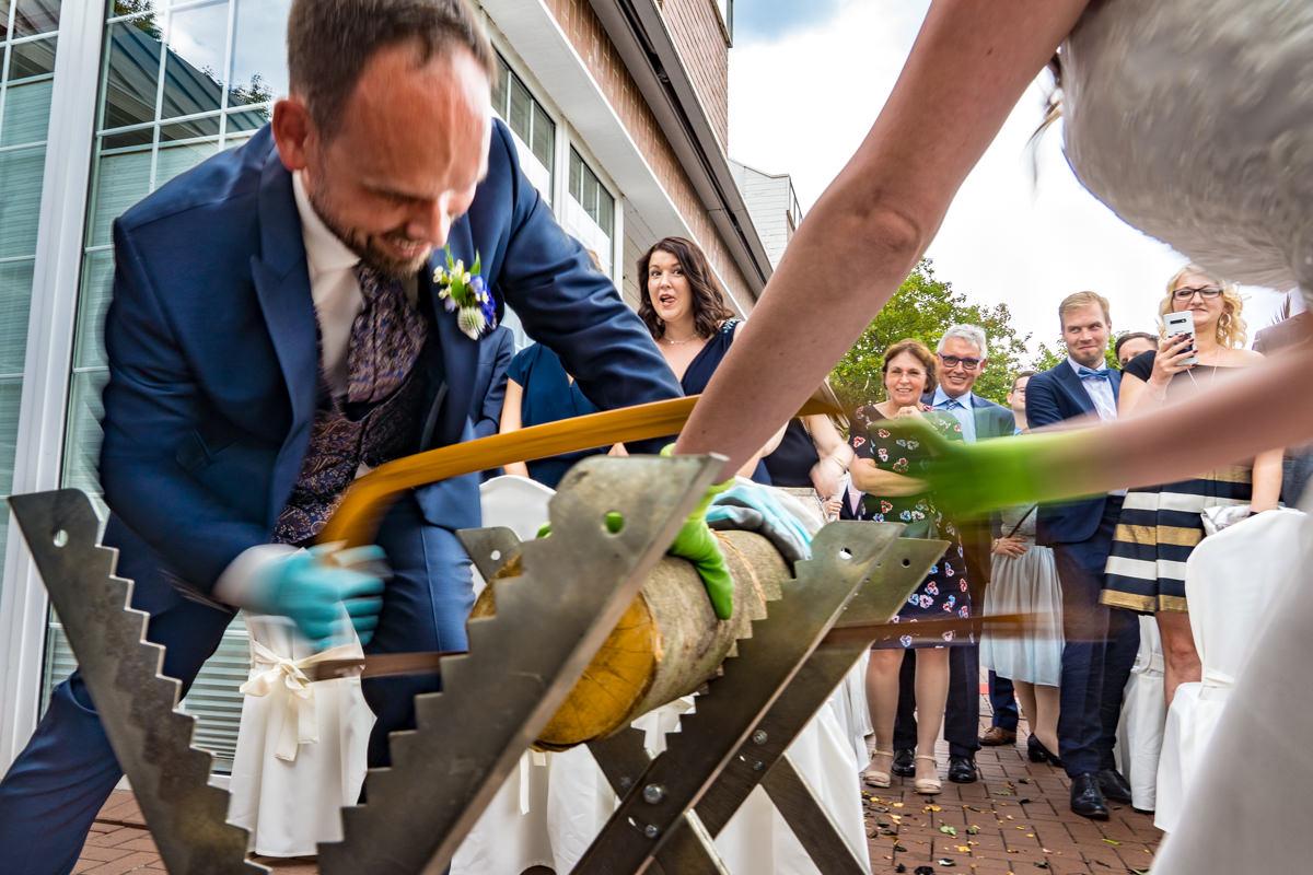 Hochzeitspaar beim Baumstammsaegen bei Trauung Haus Deichgraf Duesseldorf mit Hochzeitsfotograf Duesseldorf