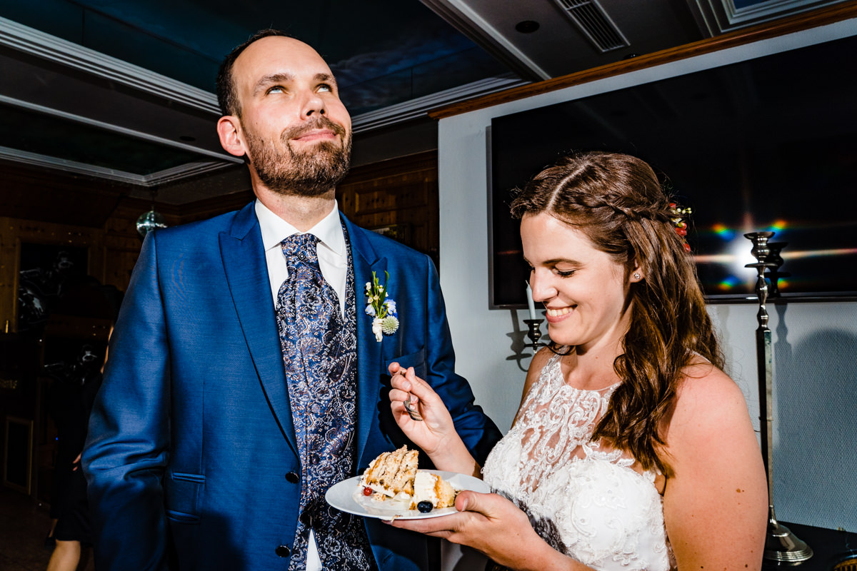 Hochzeitspaar probiert Hochzeitskuchen bei Hochzeit Deichgraf Duesseldorf mit beste Hochzeitsfotograf Duesseldorf