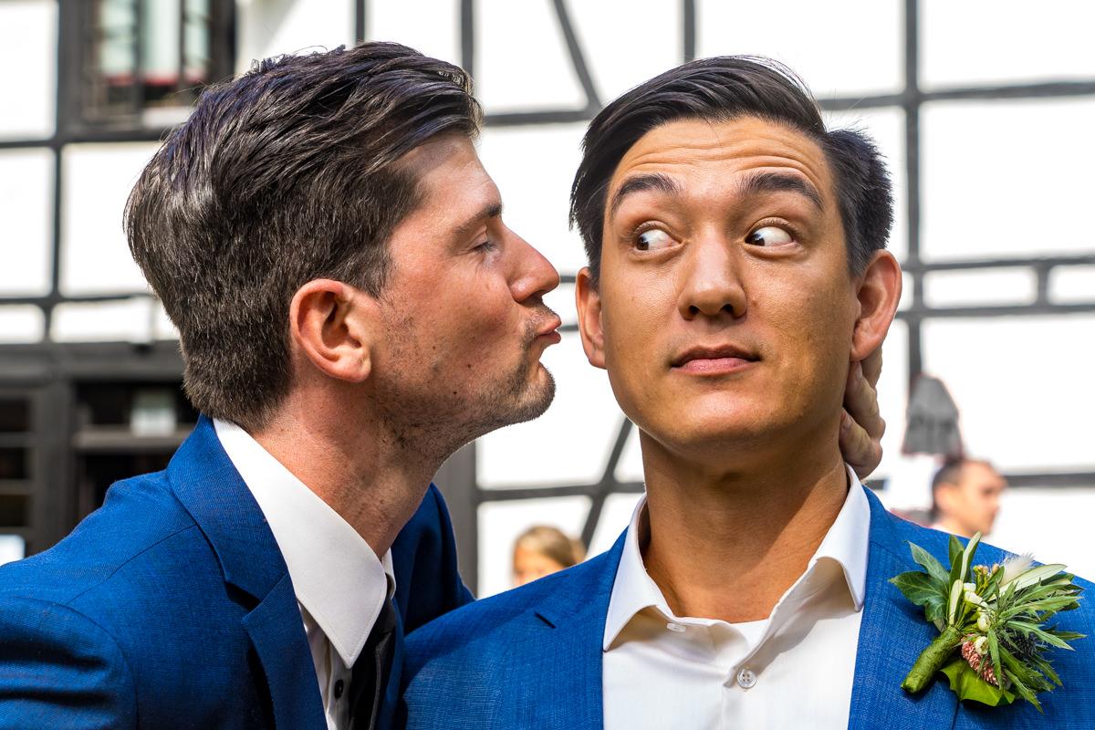 Trauzeuge kuesst Braeutigam mit Hochzeitsfotograf Solingen