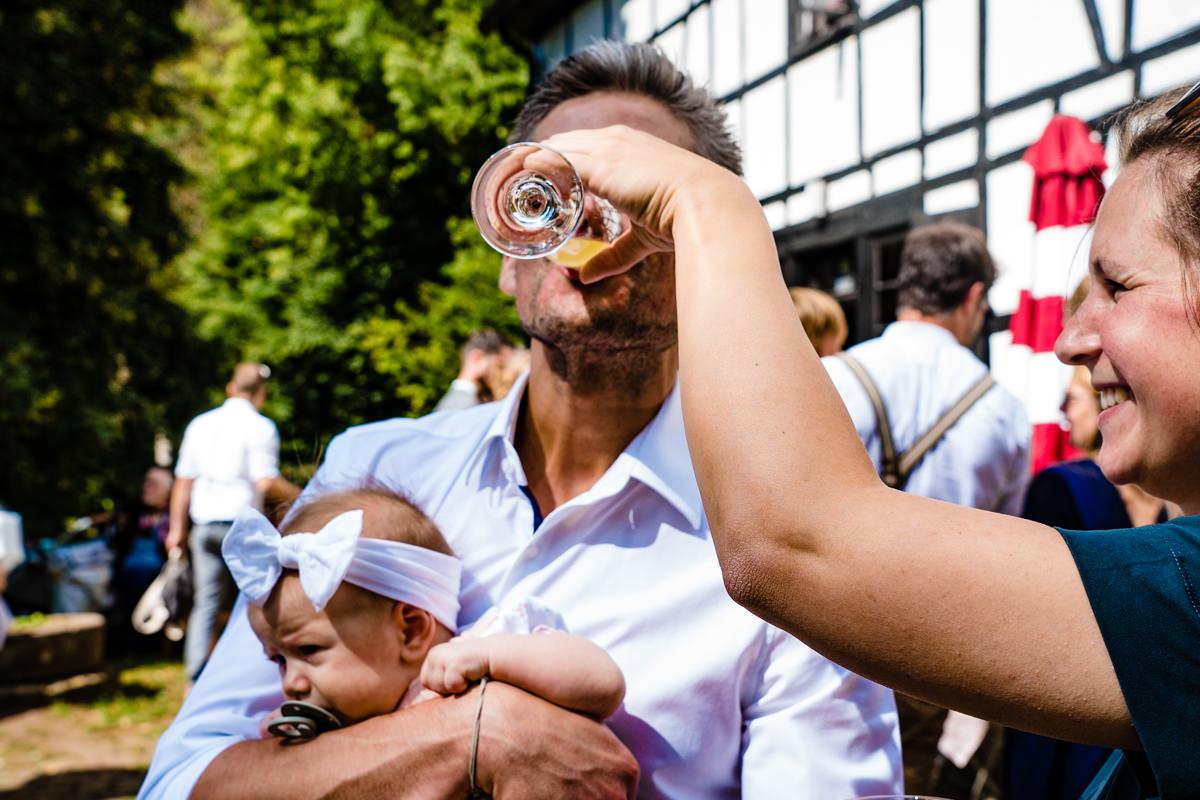 Vater mit Baby trink Sekt bei Hochzeit Balkhauser Kotten mit Hochzeitsfotograf Solingen